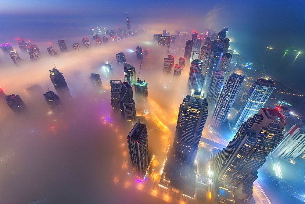 Aerial view of cityscape with illuminated skyscrapers above the clouds in Dubai, United Arab Emirates at dusk, Dubai, United Arab Emirates