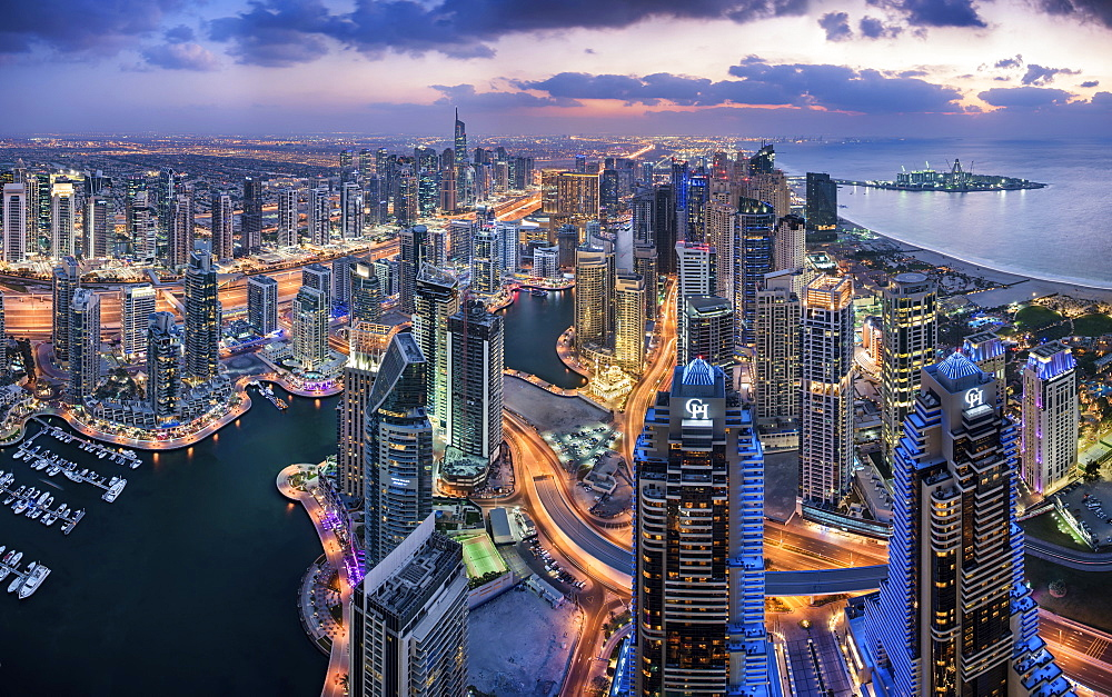 Aerial view of the cityscape of Dubai, United Arab Emirates at dusk, with illuminated skyscrapers and the marina in the foreground, Dubai, United Arab Emirates