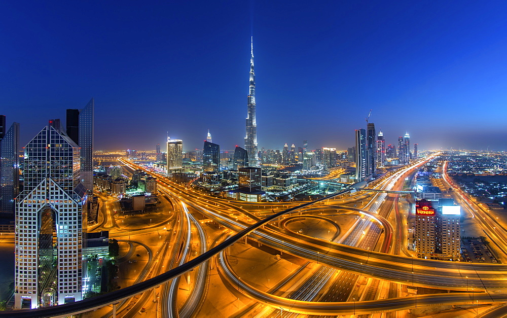 Cityscape of Dubai, United Arab Emirates at dusk, with the Burj Khalifa skyscraper and illuminated highways in the foreground, Dubai, United Arab Emirates