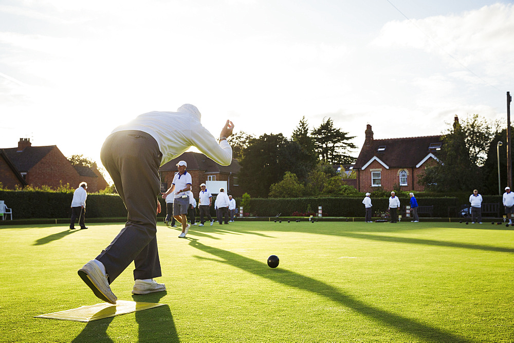 A lawn bowls player standing on a small yellow mat preparing to deliver a bowl down the green, the smooth grass playing surface, England, United Kingdom