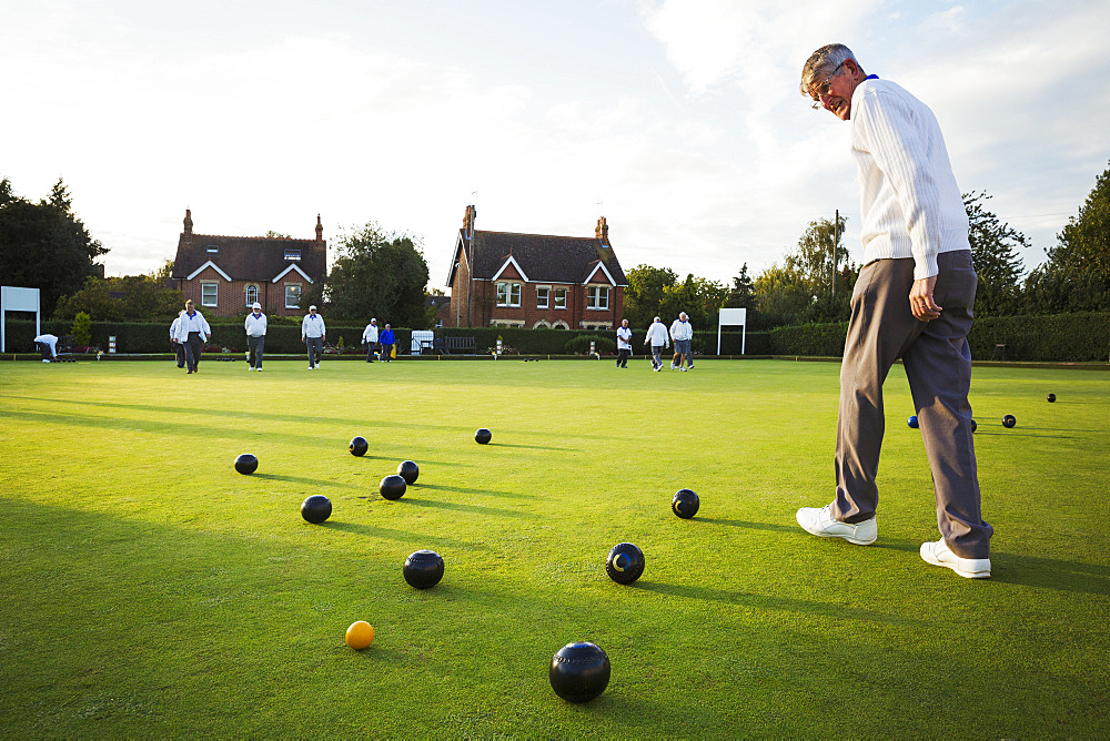 A lawn bowls player walking across the green, the playing surface, at an end with bowls clustered around the yellow jack ball, England, United Kingdom