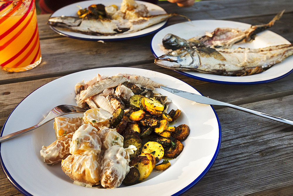 A meal outdoors at a wooden table, plates with grilled mackerel fish, vegetables and potatoes. A drinking glass, England, United Kingdom - 1174-4552
