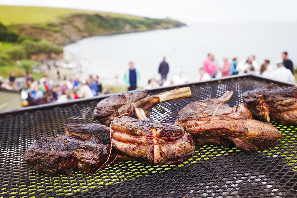 A beach barbecue with meat cooking over an open fire. People in the background on the cliffs overlooking the coastline, England, United Kingdom