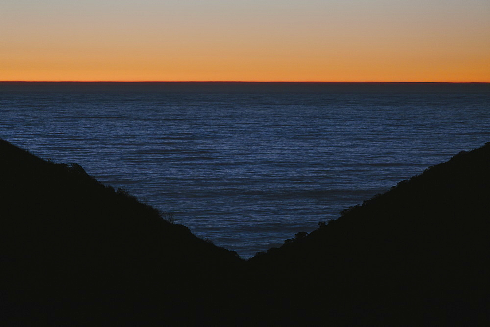 Seascape with ocean at dusk, hills in foreground.