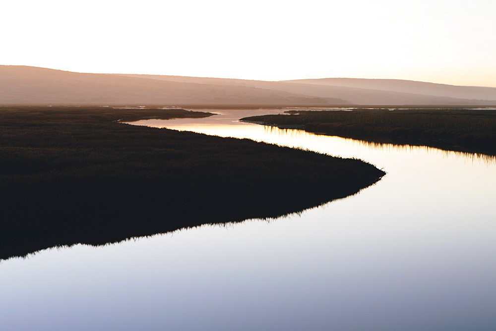 The open spaces of marshland and water channels. Flat calm water.  Dusk.