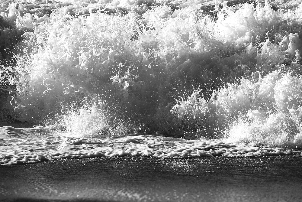Waves crashing and breaking on the shore.