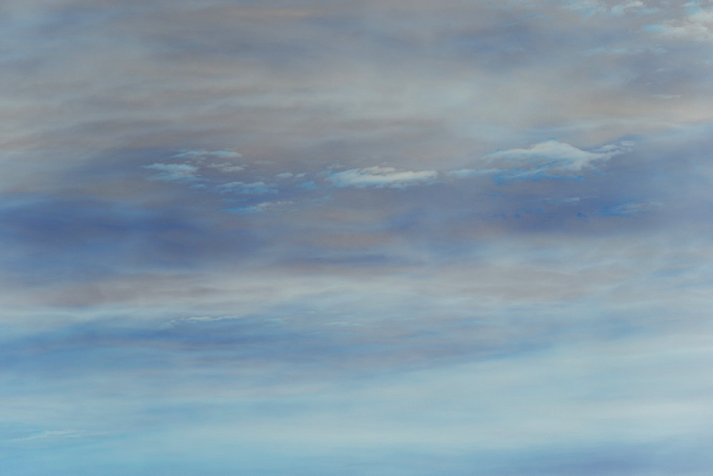 Abstract of blue and purple sky with clouds at dusk.