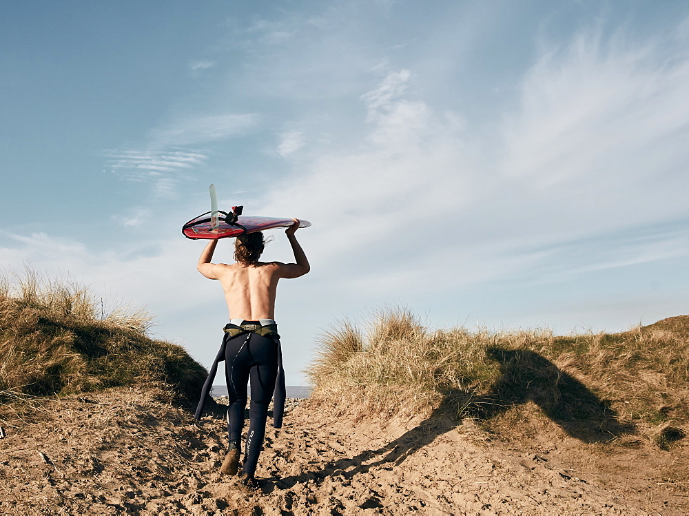 Man walking on a path in the sand dunes towards sea with surf board balancing on his head, United Kingdom - 1174-4695