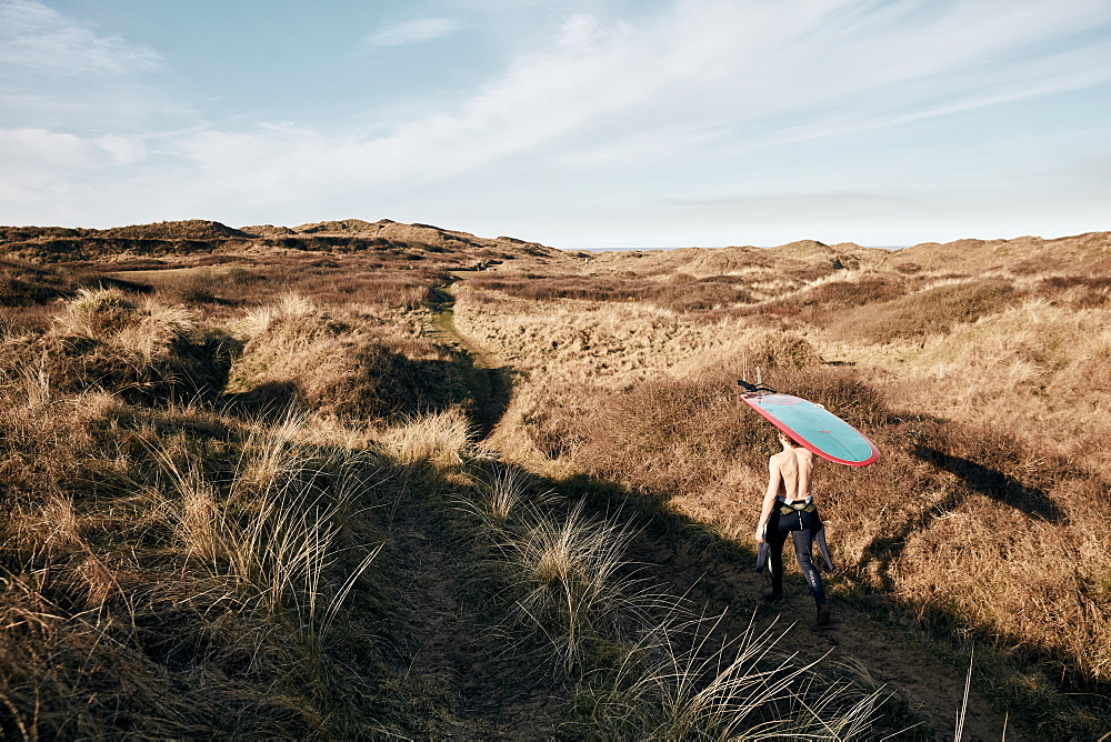 Man walking on a path in the sand dunes towards sea with surf board balancing on his head, United Kingdom - 1174-4696