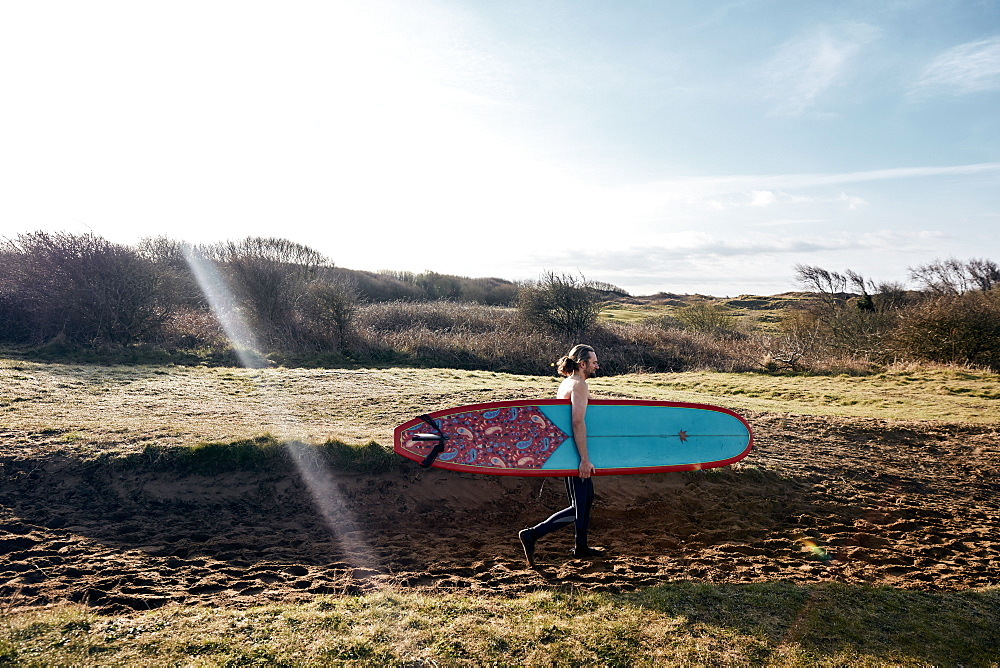 Man holding surf board walking along sandy path towards the sea, United Kingdom - 1174-4698