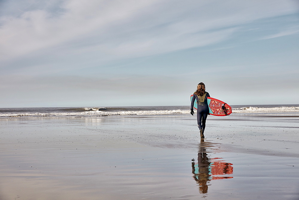 Man holding a surf board walking out to the sea at low tide, United Kingdom