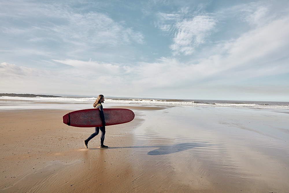 Man in a wetsuit walking towards sea holding a surf board, United Kingdom