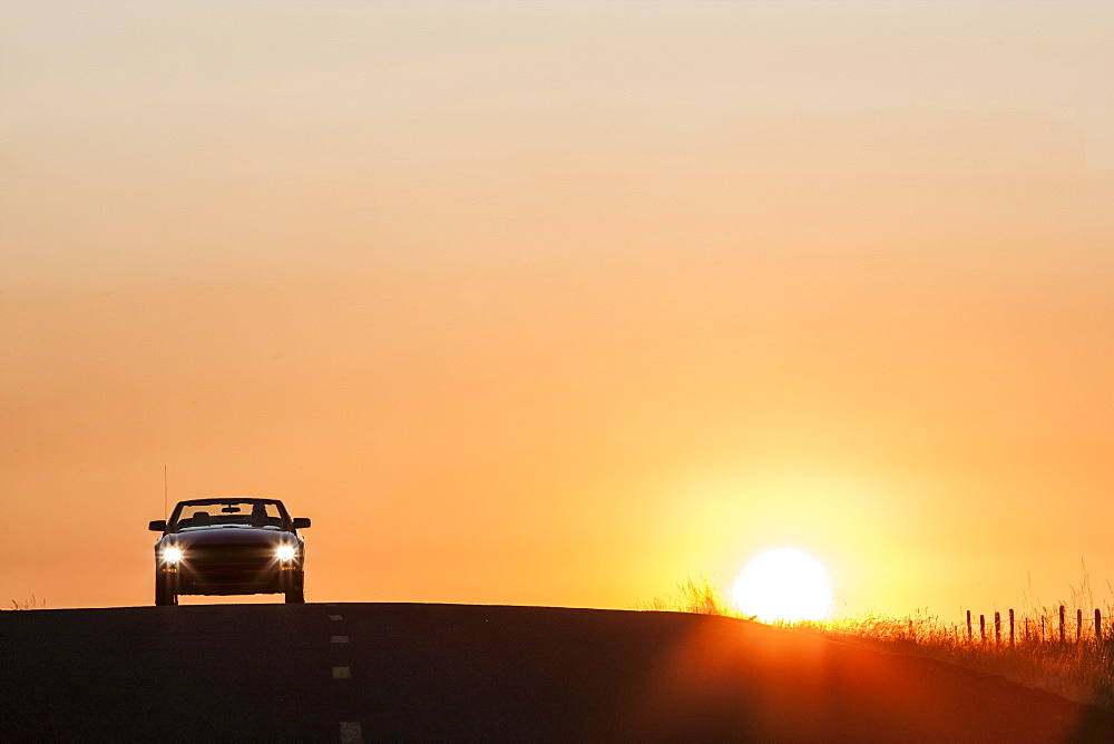 A convertible sports car on a country highway at sunset, United States of America