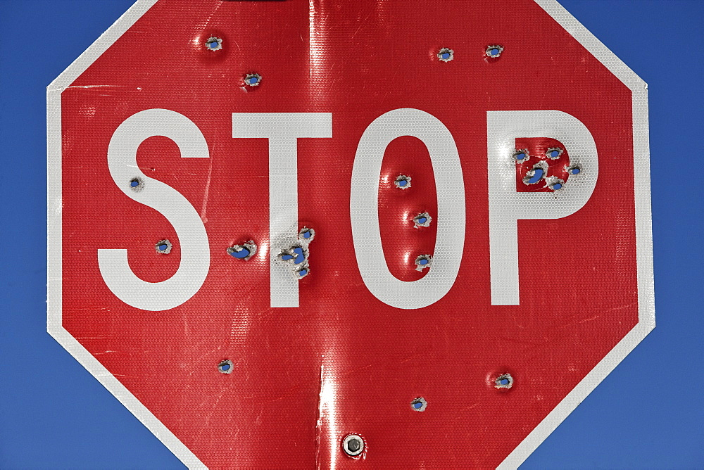 A stop sign that has been shot multiple times with a high powered rifle, United States of America - 1174-4713