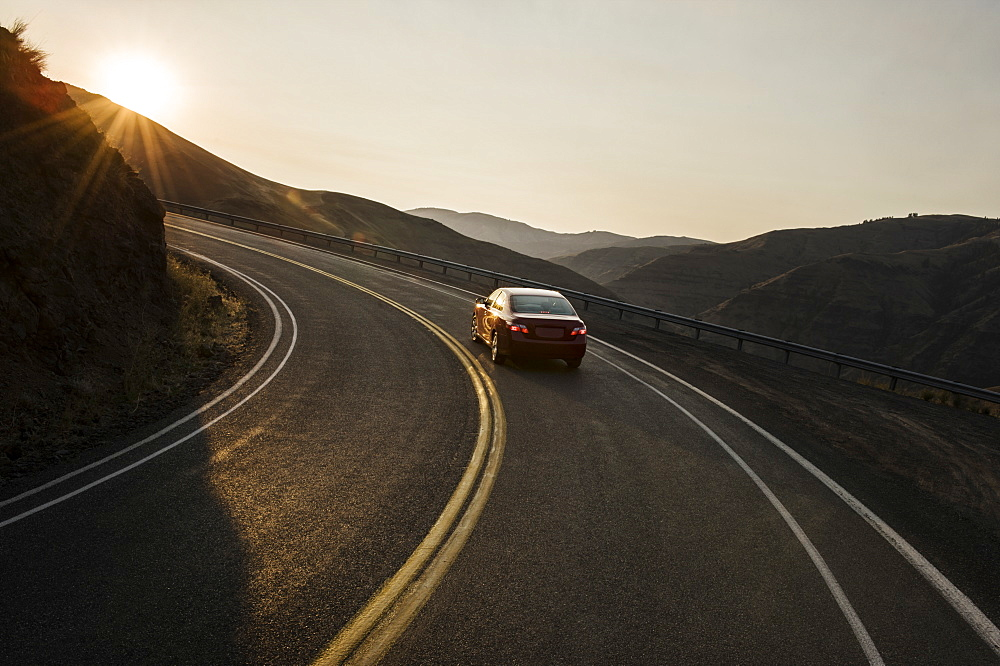 A view from behind of an automobile going around a curve at sunset in eastern Washington State, United States of America