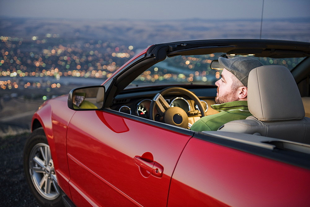 A Caucasian male parked in his convertible sports car watching the sunset over the Clearwater River and the city of Lewiston Idaho, United States of America - 1174-4718