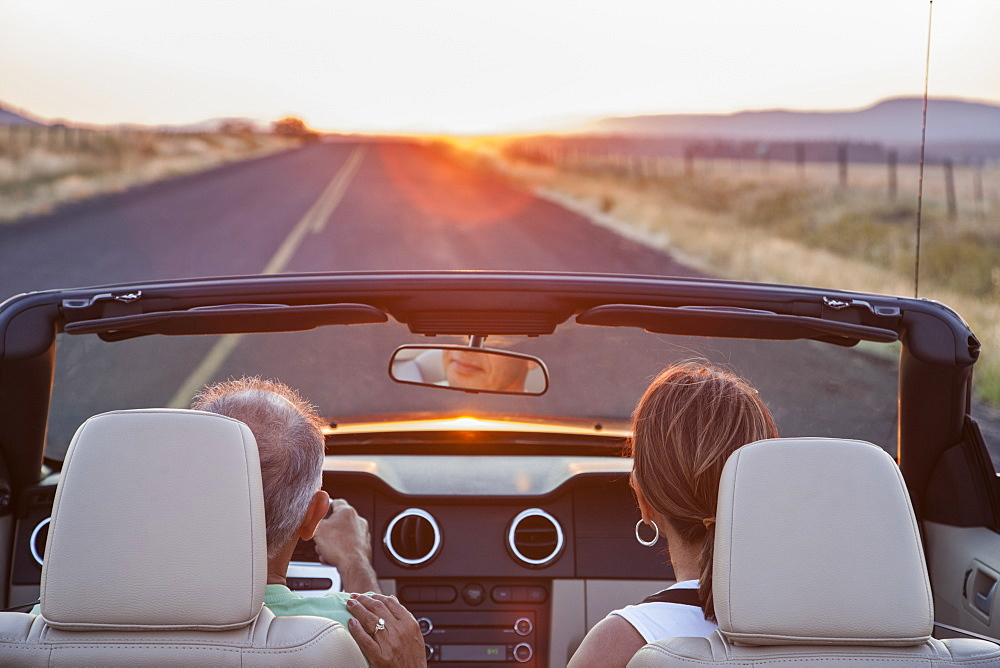 View from behind of senior couple in a convertible sports car driving on a highway at sunset in eastern Washington State, United States of America