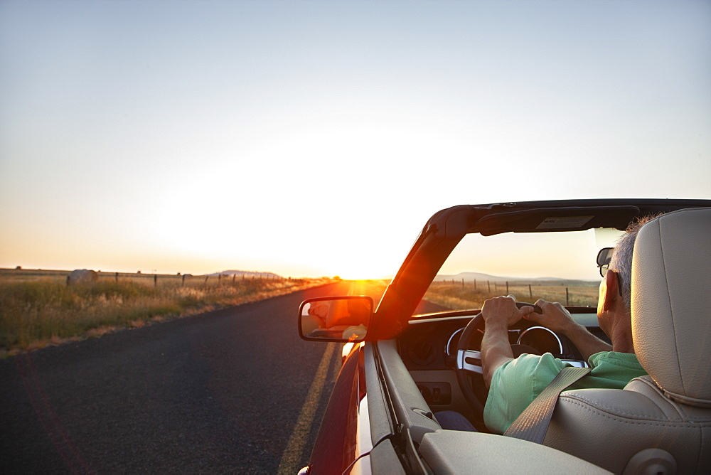 A senior Hispanic man at the wheel of his convertible sports car at sunset in eastern Washington State, United States of America