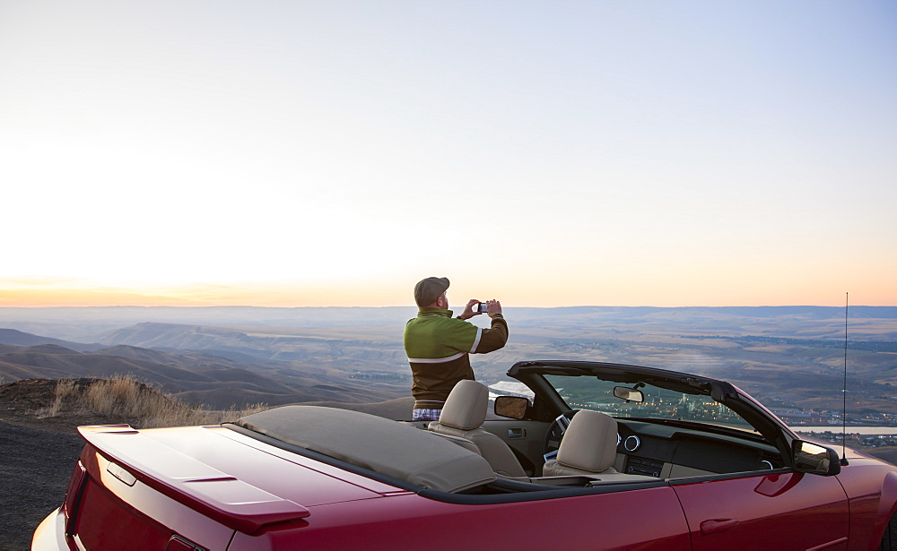 A driver stops to take a photograph at sunset near Lewiston, Idaho, USA on a road trip with his convertible sports car, United States of America