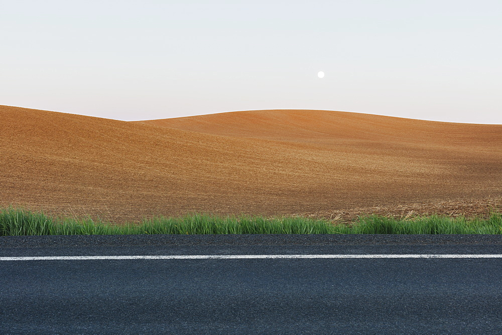 Moonrise over rolling freshly planted fields, road in foreground, Washington, United States of America