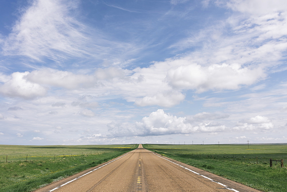 Open road through vast prairie and farmland, Saskatchewan, Canada