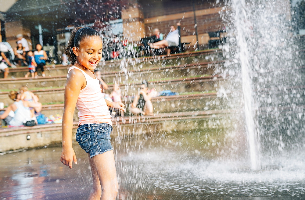 Smiling girl playing in public fountain in summer, United States of America