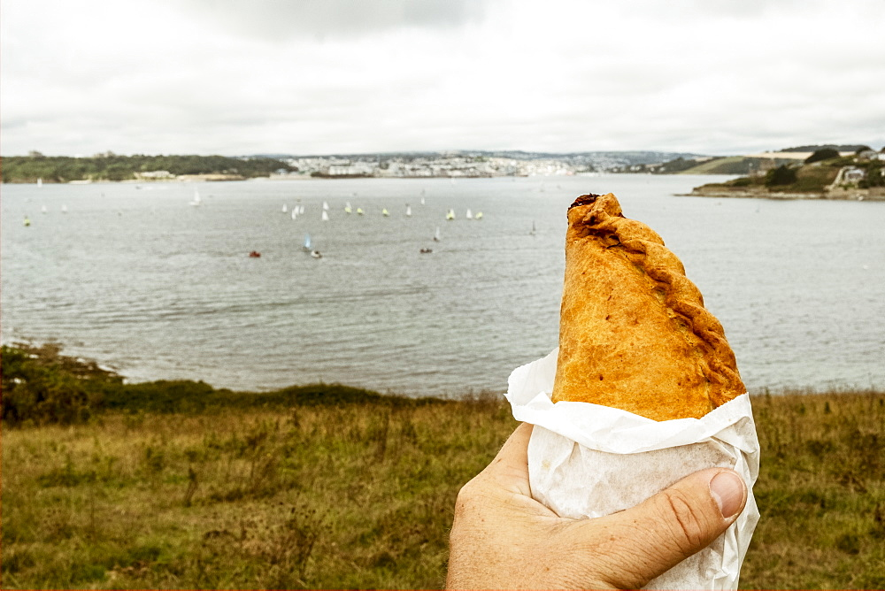 A hand holding a Cornish pasty baked pastry with a crimped edge, seated overlooking a sea estuary, Cornwall, England