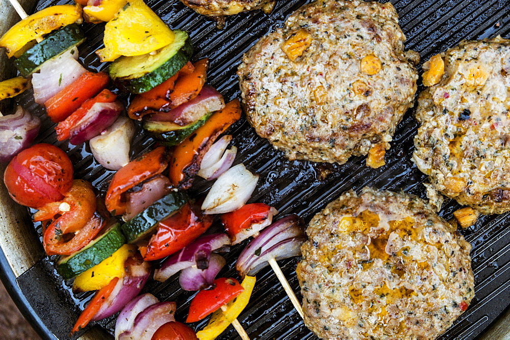 Food on a barbeque, vegetable kebabs and home made burgers, cooking outdoors, Wales - 1174-4806
