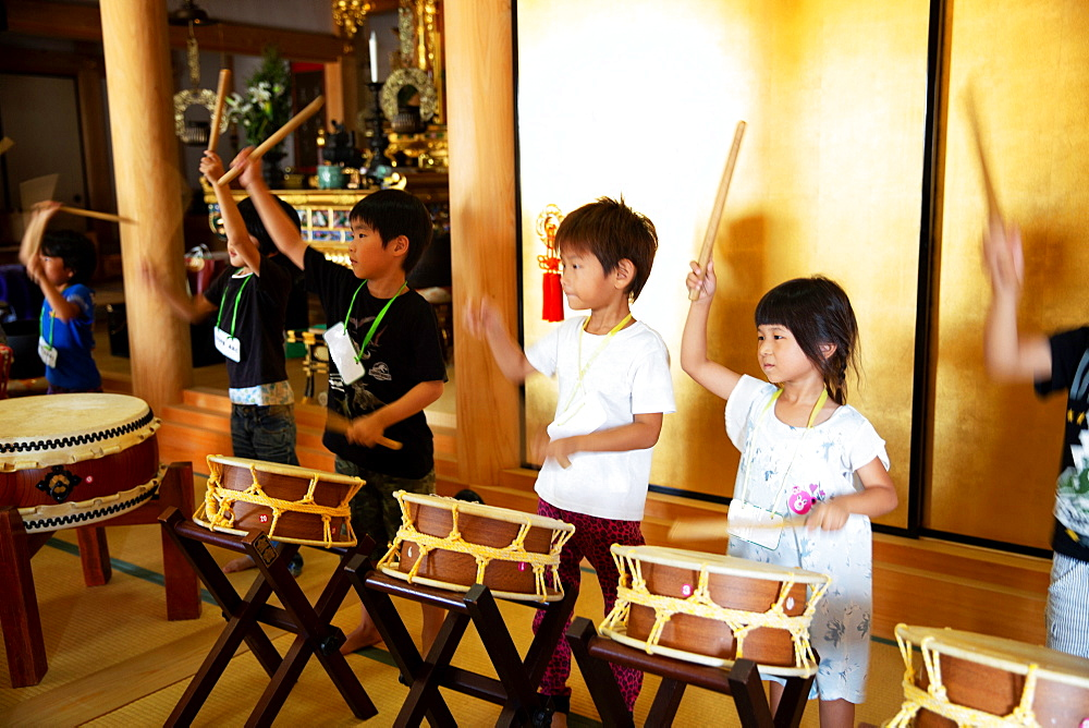 Group of pre-school children playing the drums in a Japanese temple, a traditional religious practise, Kyushu, Japan