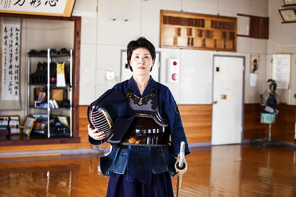 Female Japanese Kendo fighter standing in a gym, holding Kendo mask and sword, looking at camera, Kyushu, Japan