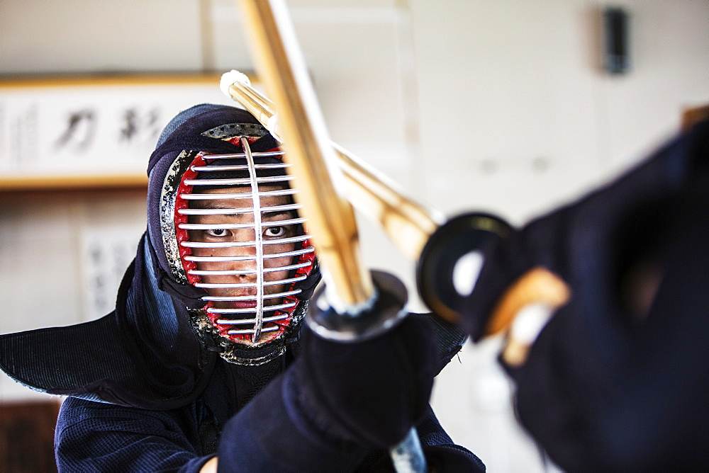 Close up of Japanese Kendo fighter wearing Kendo mask in combat pose, Kyushu, Japan