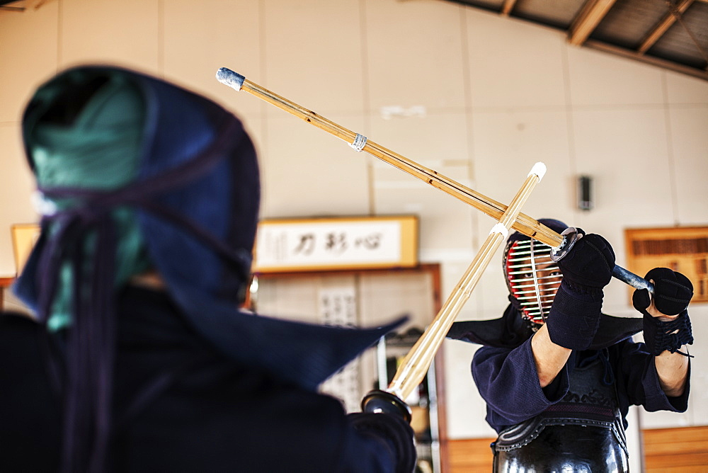 Two Japanese Kendo fighters wearing Kendo masks practicing with wood sword in gym, Kyushu, Japan