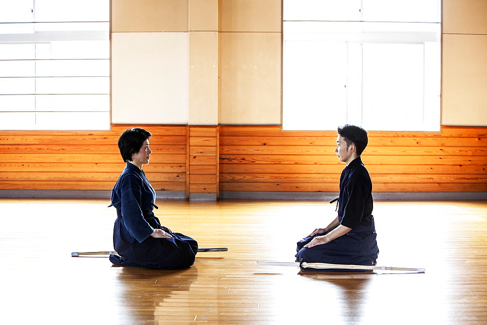 Female and male Japanese Kendo fighters kneeling opposite each other on wooden floor, Kyushu, Japan