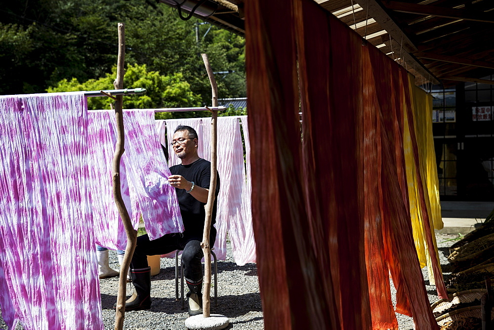 Japanese man sitting outside a textile plant dye workshop, hanging up freshly dyed pink fabric, Kyushu, Japan