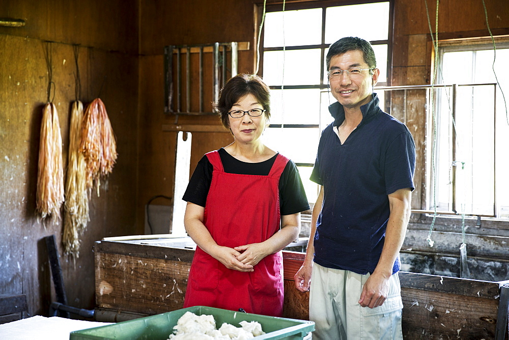 Japanese woman and man standing in a Washi workshop by a vat of pulp, basic plant based ingredients for making paper, Kyushu, Japan