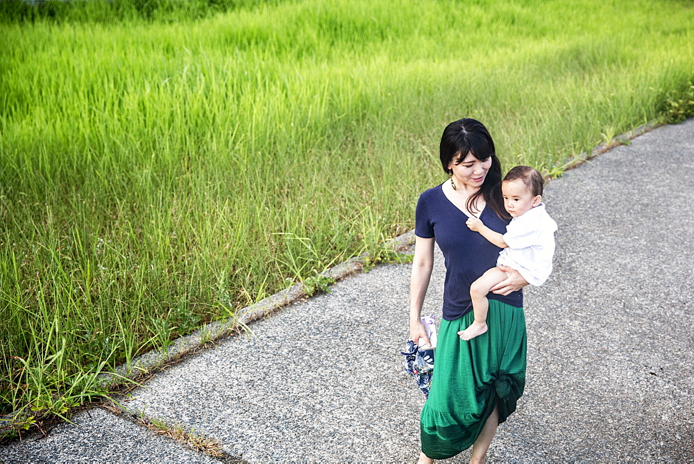 Japanese woman carrying young boy walking along a concrete path through tall grass, Kyushu, Japan