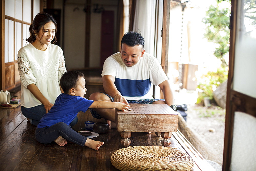 Japanese woman, man and little boy sitting on floor on porch of traditional Japanese house, playing Go, Kyushu, Japan