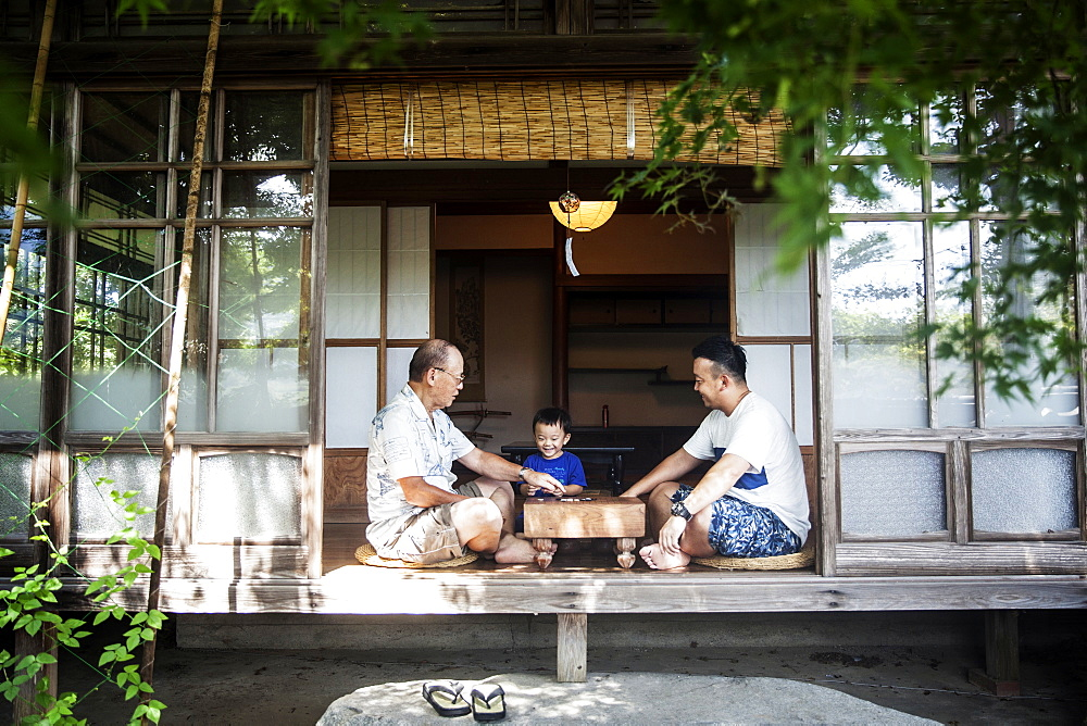 Two Japanese men and little boy sitting on floor on porch of traditional Japanese house, playing Go, Kyushu, Japan