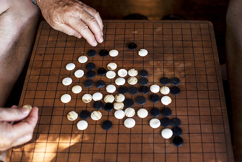 High angle close up wooden Go board with black and white gaming pieces, Kyushu, Japan