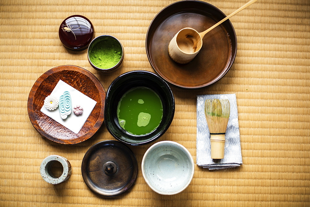 Tea ceremony utensils including bowl of green Matcha tea, a bamboo whisk and Wagashi sweets, Kyushu, Japan