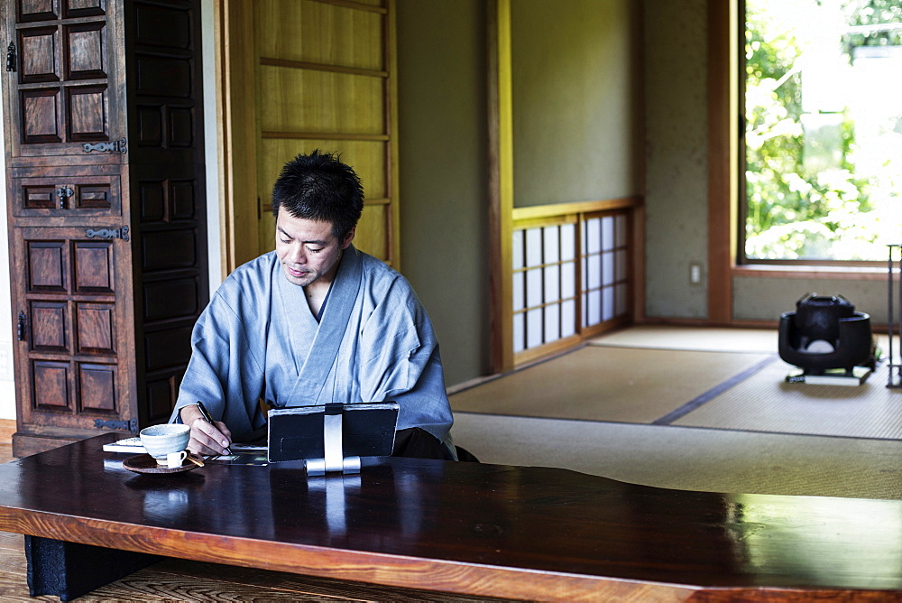 Japanese man wearing kimono sitting on floor in traditional Japanese house, looking at digital tablet, Kyushu, Japan