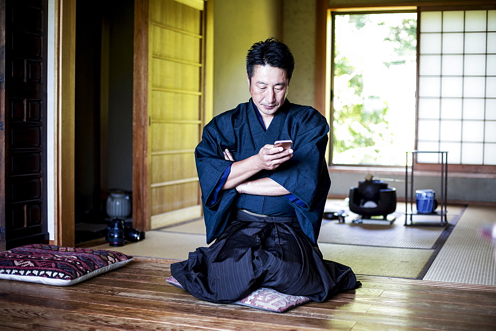 Japanese man wearing kimono sitting on floor in traditional Japanese house, using mobile phone, Kyushu, Japan