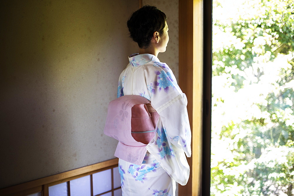 Rear view of Japanese woman standing at window, wearing traditional white kimono with blue floral pattern and pink obi, Kyushu, Japan