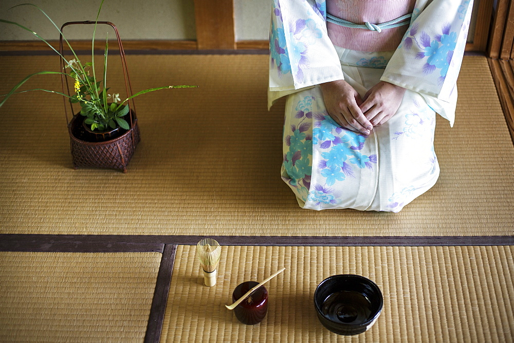 Japanese woman wearing traditional white kimono with blue floral pattern kneeling on tatami mat in front of bowl and whisk for tea ceremony, Kyushu, Japan