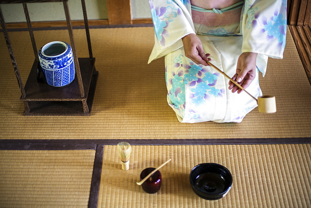 High angle view of Japanese woman wearing traditional white kimono with blue floral pattern kneeling on tatami mat during tea ceremony, holding a Hishaku, a bamboo ladle, Kyushu, Japan