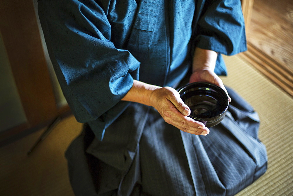High angle close up of Japanese man wearing kimono holding tea bowl during tea ceremony, Kyushu, Japan