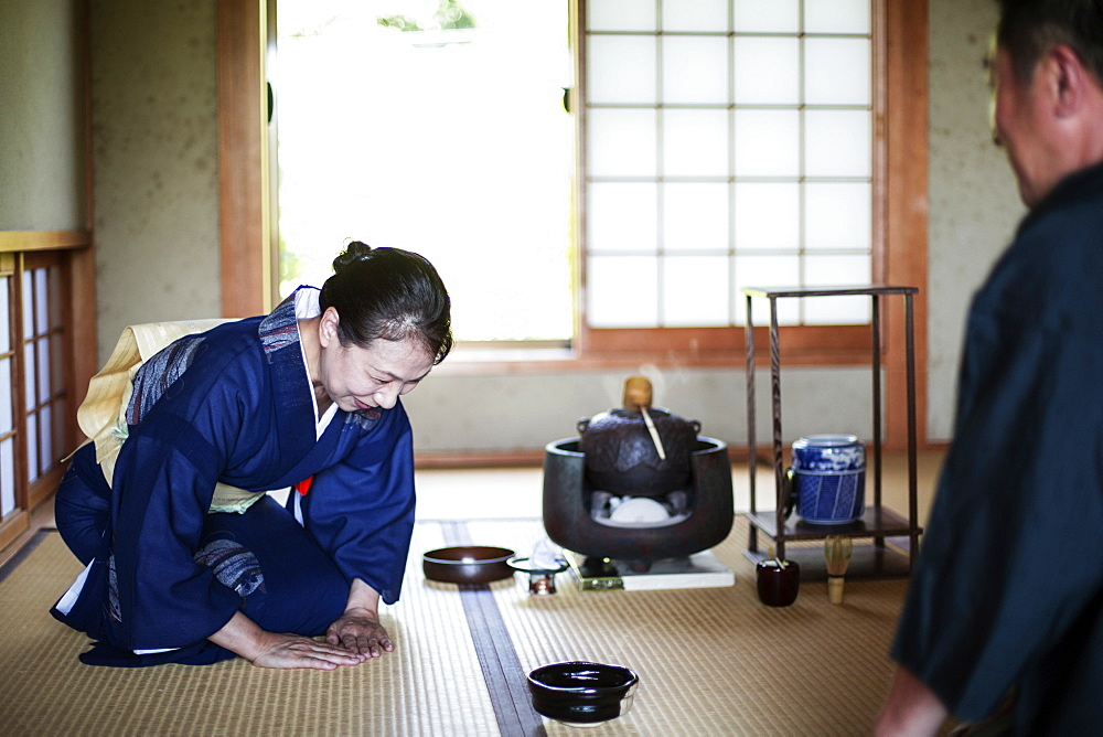 Japanese woman wearing traditional bright blue kimono with cream coloured obi and man kneeling on floor during tea ceremony, Kyushu, Japan