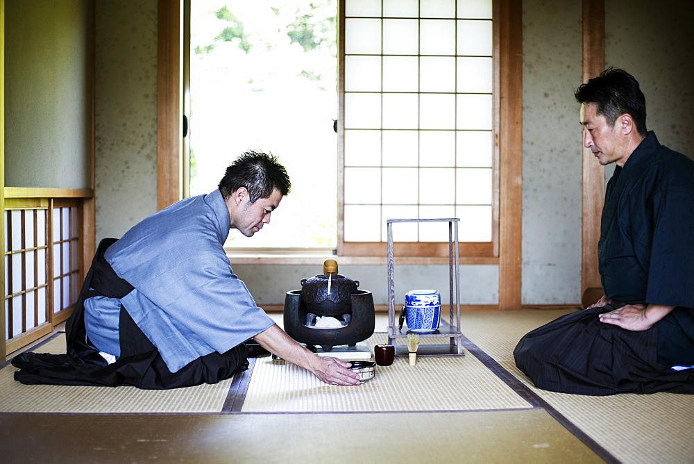 Two Japanese men wearing traditional kimonos kneeling on floor during tea ceremony, Kyushu, Japan - 1174-4918