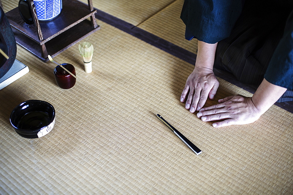 High angle close up of Japanese man kneeling on tatami mat in front of Sensu fan, bowl and whisk used in tea ceremony, Kyushu, Japan