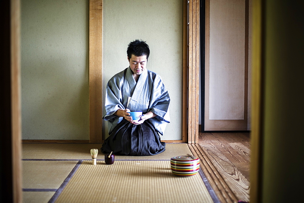 Japanese man wearing traditional kimono kneeling on tatami mat, holding tea bowl, during tea ceremony, Kyushu, Japan